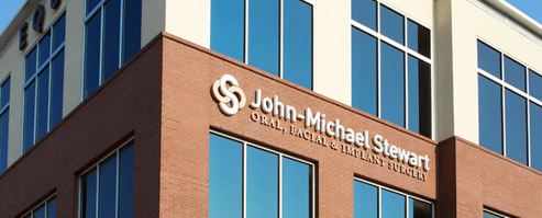 JMS OralJohn-Michael Stewart office windows and exterior with sign high on the wall Surgery