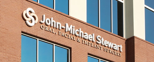 John-Michael Stewart office windows and exterior with sign high on the wall - JMS Oral Surgery